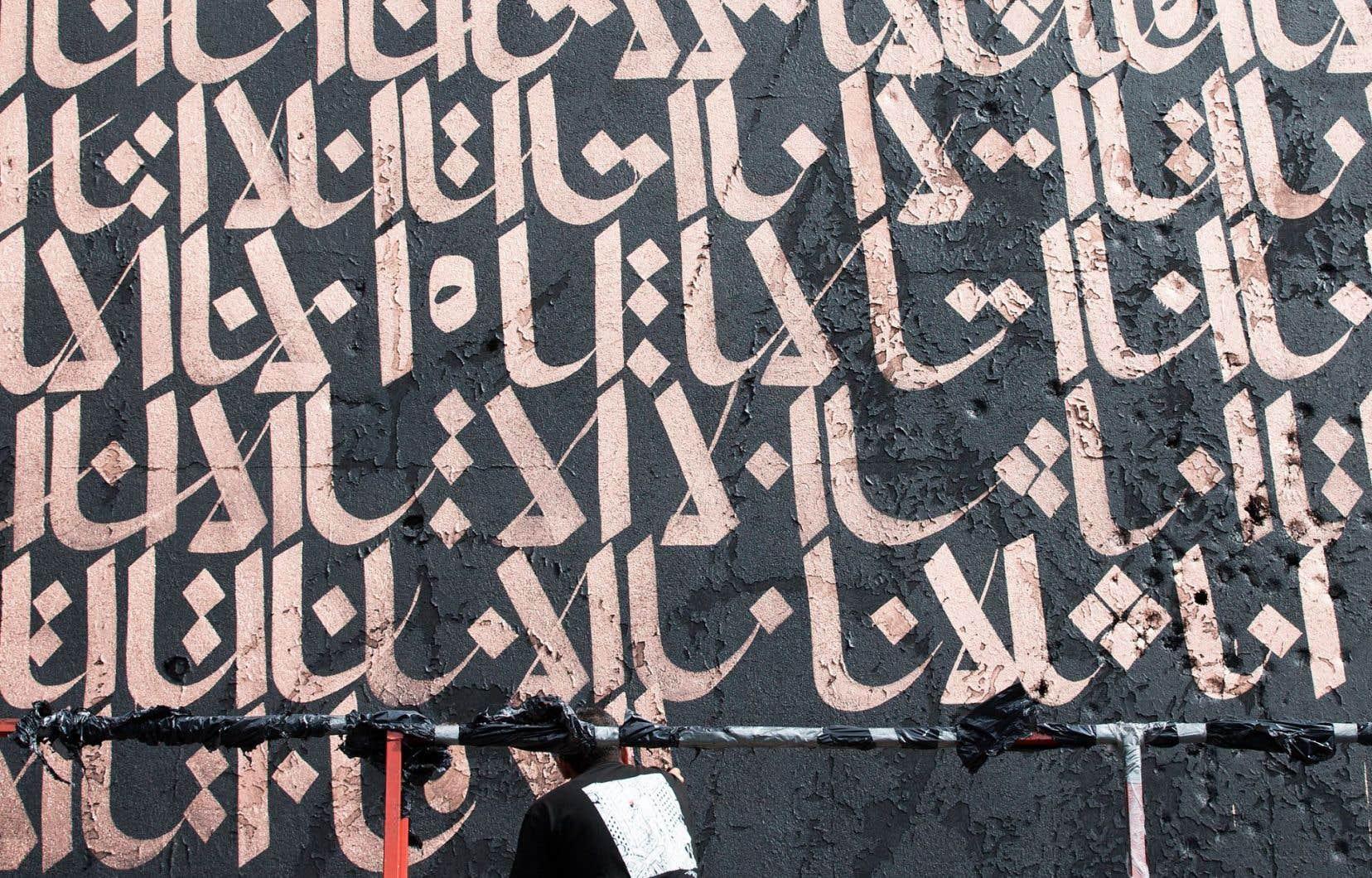 L'artiste Karim Jabbari trace les lettres en kufi classique, l'une des plus anciennes formes d'écriture de cette langue. Elles formeront un motif précis qui évoquera l'unité.