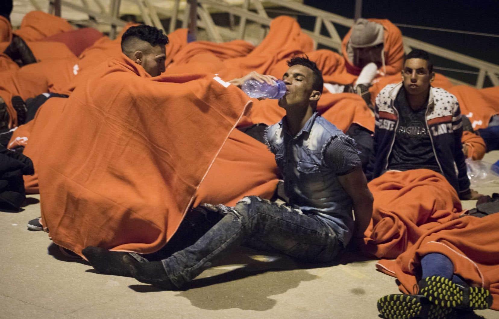 Un migrant marocain abreuve un autre homme alors qu'ils se reposent au port de Barbate, après avoir été secourus dans les eaux du détroit de Gibraltar, au large de la côte espagnole, le 7 juillet 2017.