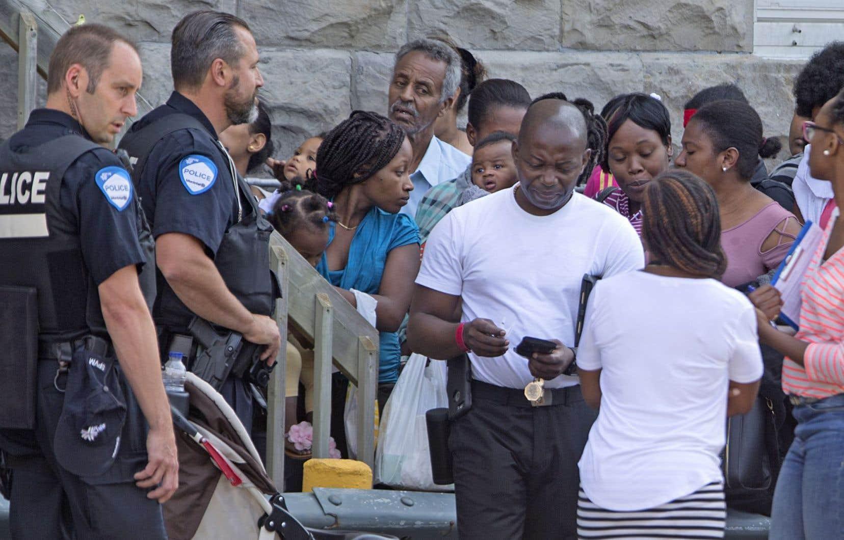 À Montréal, mercredi, des demandeurs d'asile ont fait la queue devant les nouveaux locaux du Programme régional d'accueil et d'intégration des demandeurs d'asile pour y remplir les documents nécessaires à leur requête.