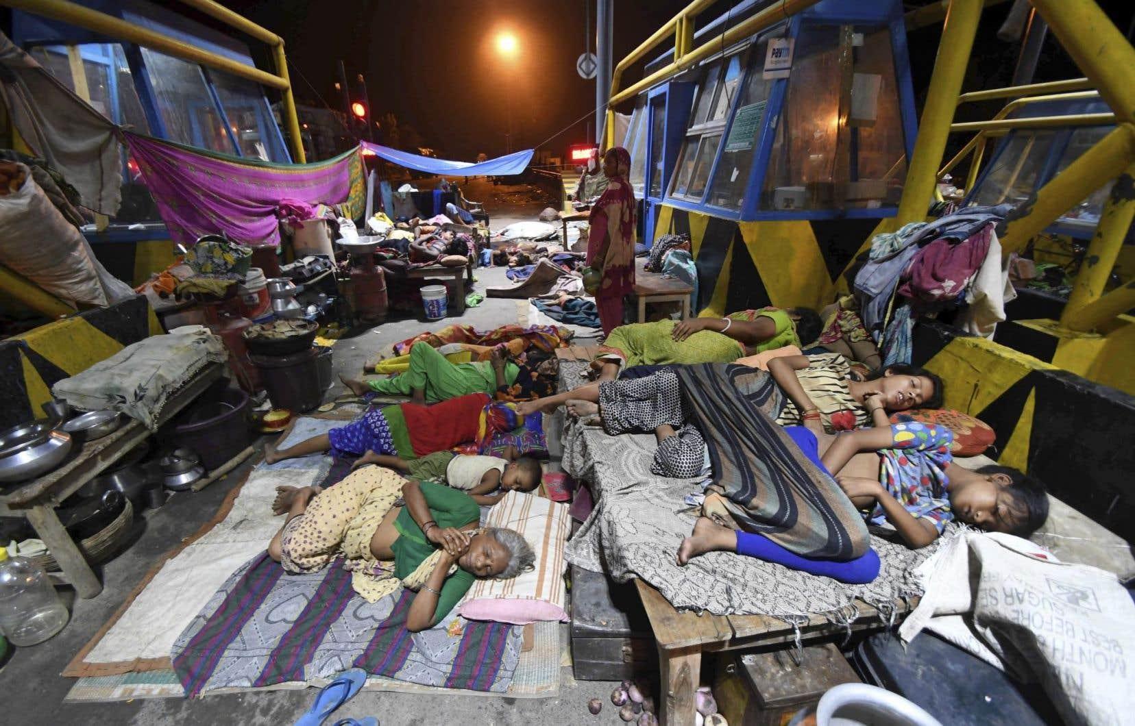 Des personnes rescapées des inondations dorment près d'un poste de péage routier dans le district d'Araria, dans l'État indien de Bihar.