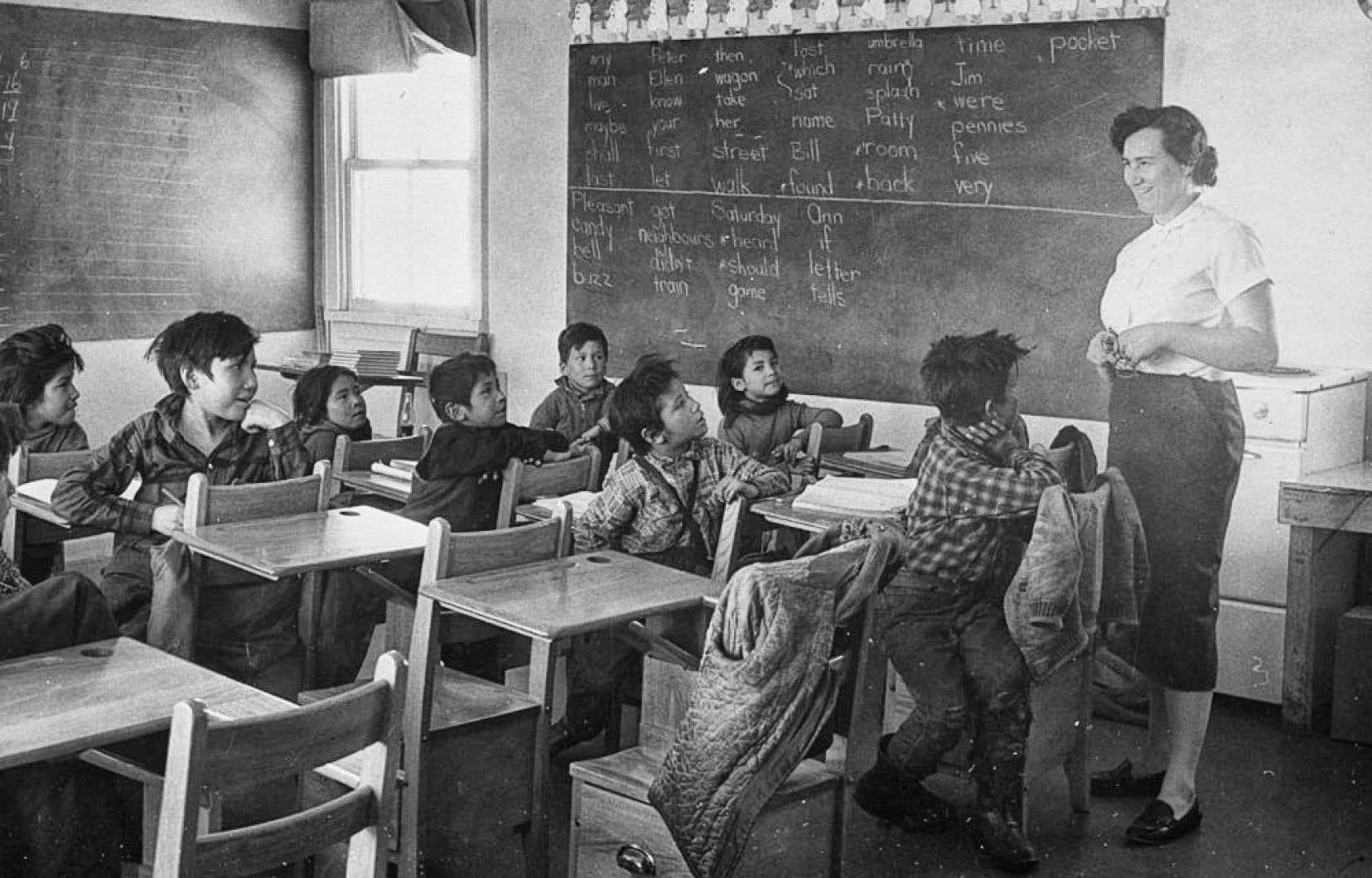 Un groupe d'enfants naskapis dans une salle de classe. Le responsable des Affaires indiennes lors de l'établissement du système de pensionnats pour autochtones était non pas Louis-Hector Langevin, mais le premier ministre de l'époque, John A. Macdonald.
