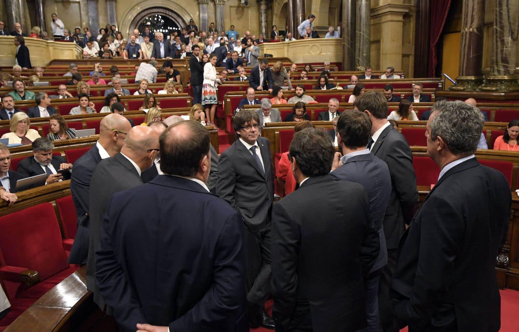 Le président catalan Carles Puigdemont, au centre, discute avec les membres de son cabinet. Après de vaines tentatives d'obtenir un référendum d'autodétermination négocié avec l'État espagnol, le gouvernement catalan a décidé d'organiser le 1eroctobre prochain un référendum unilatéral.
