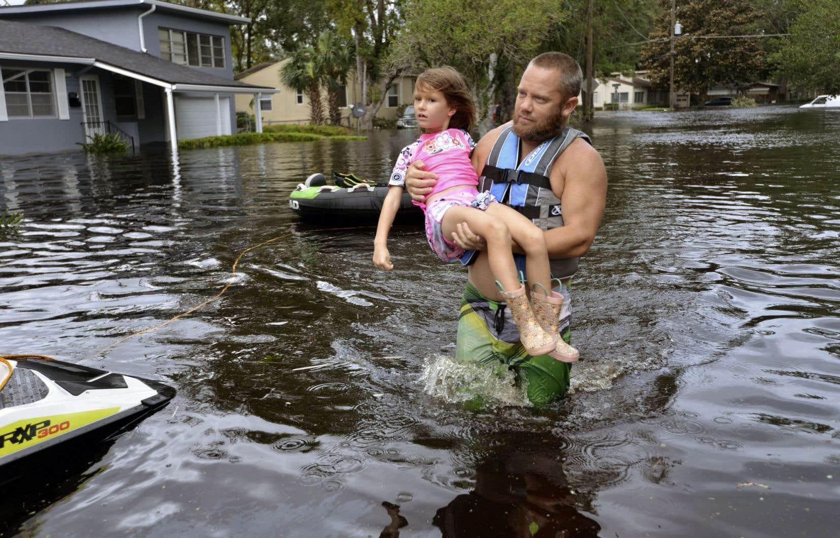 À Jacksonville, en Floride, un homme transporte dans ses bras une fillette de six ans pour l'amener au sec.