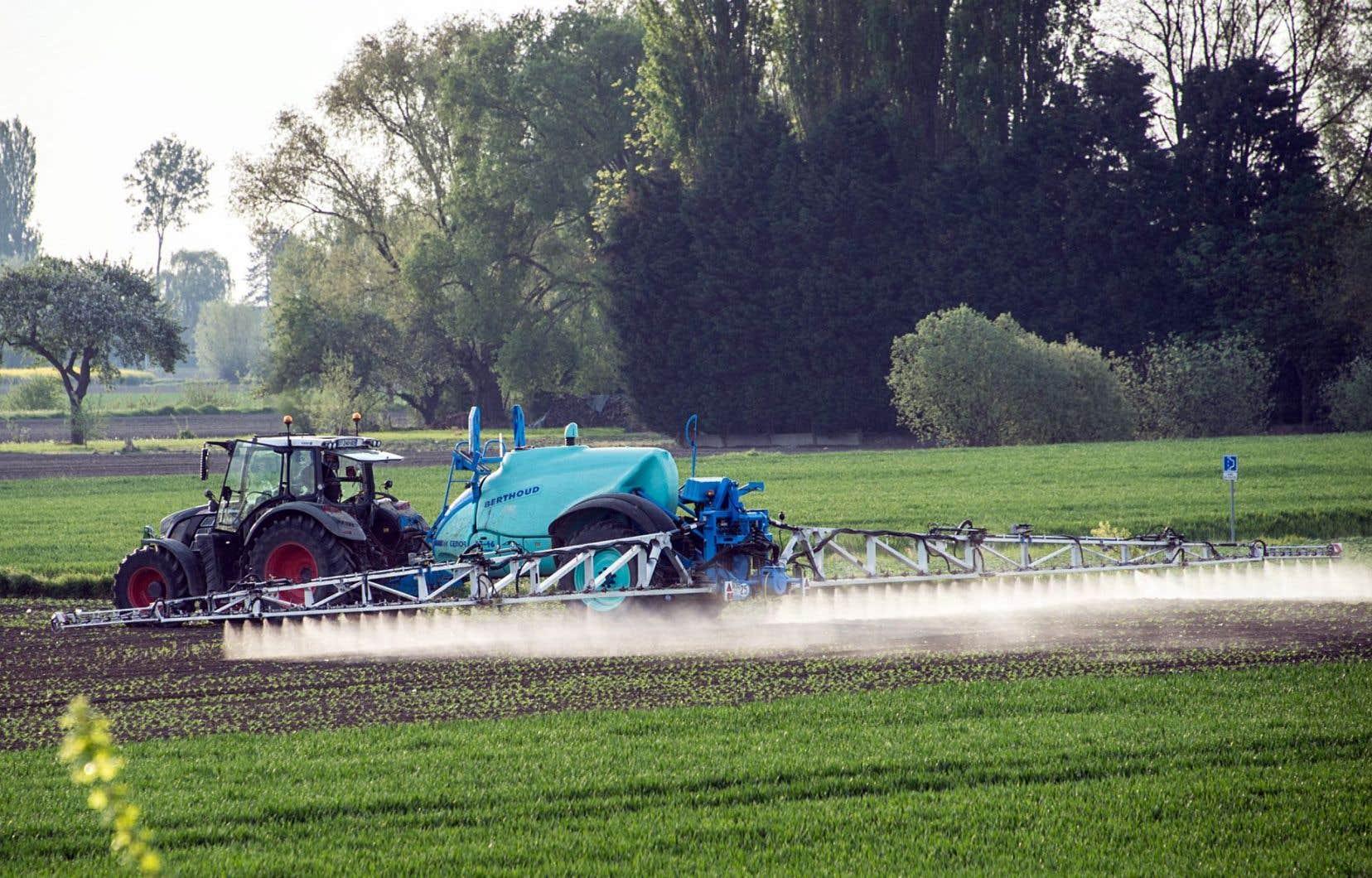 Un agriculteur épand des pesticides dans un champ pour protéger ses cultures.
