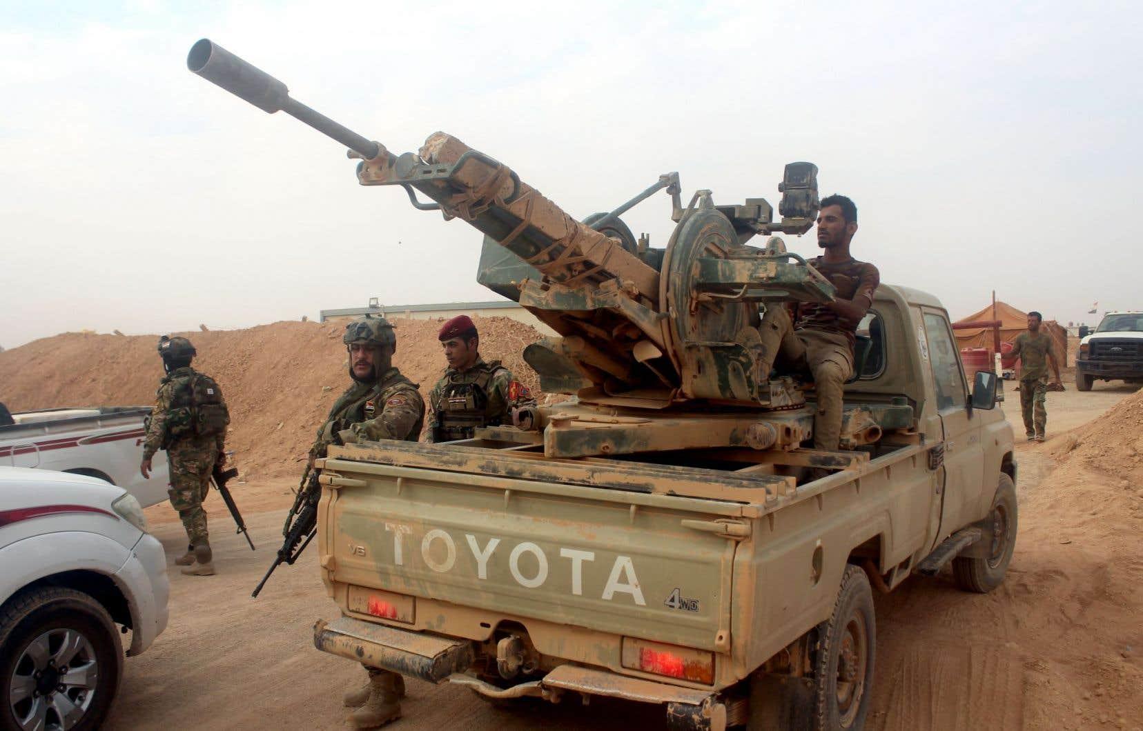 Des artilleurs à bord de leurs camions armés de mitrailleuses sont postés derrière des remblais poussiéreux.