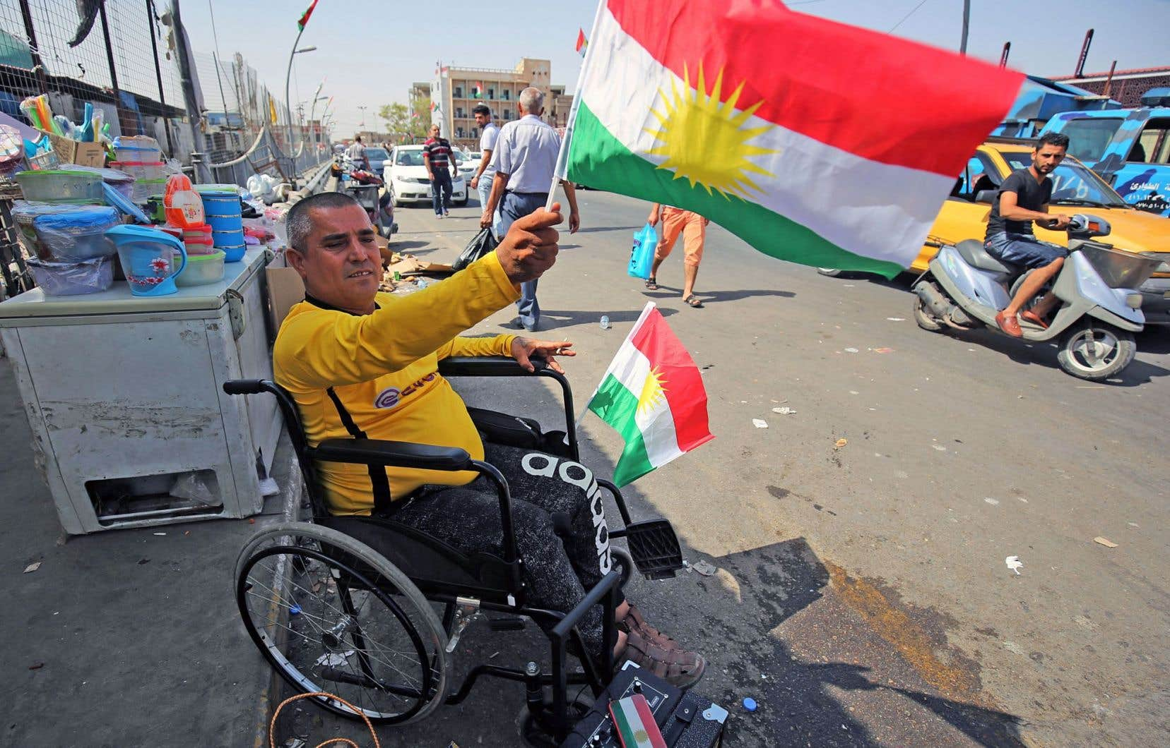 Un partisan de l'indépendance brandit un drapeau aux couleurs du Kurdistan à la veille du référendum dans la ville de Kirkouk. Les Kurdes d'Irak se déclareront lundi pour l'indépendance ou non de la région autonome du Nord.