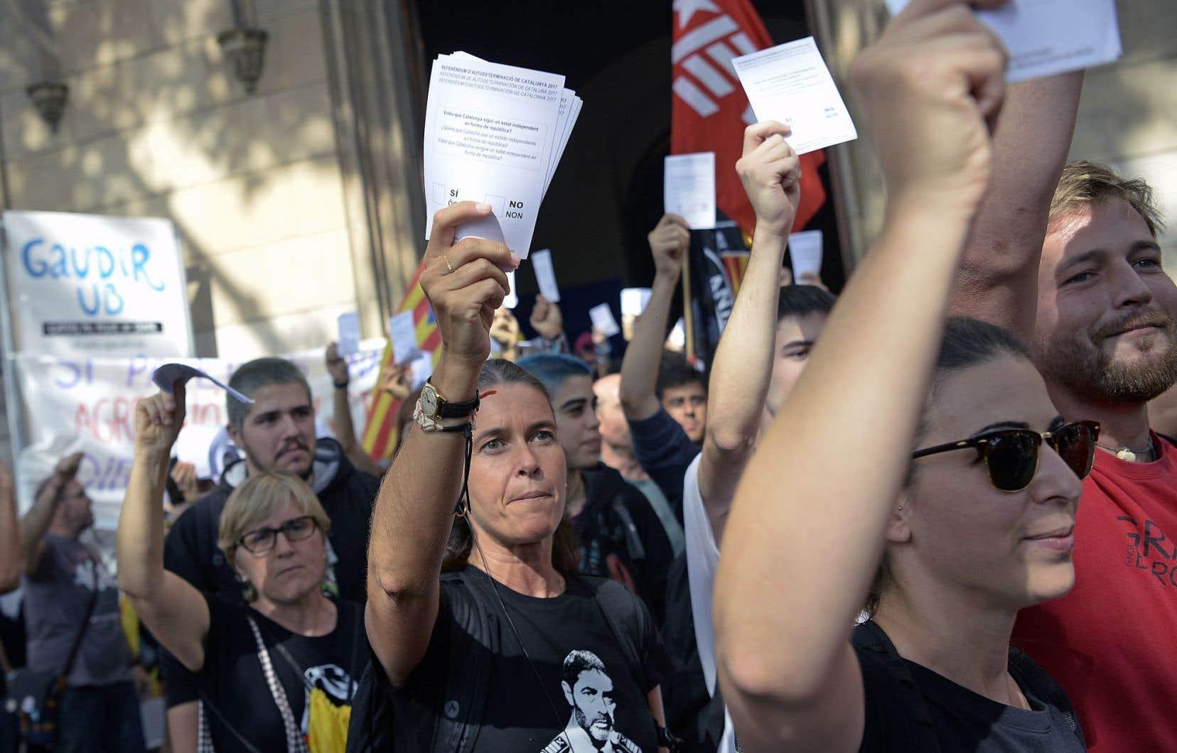 Des militants séparatistes brandissent des affiches en soutien à la tenue du scrutin prévu par le gouvernement catalan pour le 1eroctobre, durant une manifestation à Barcelone, dimanche.