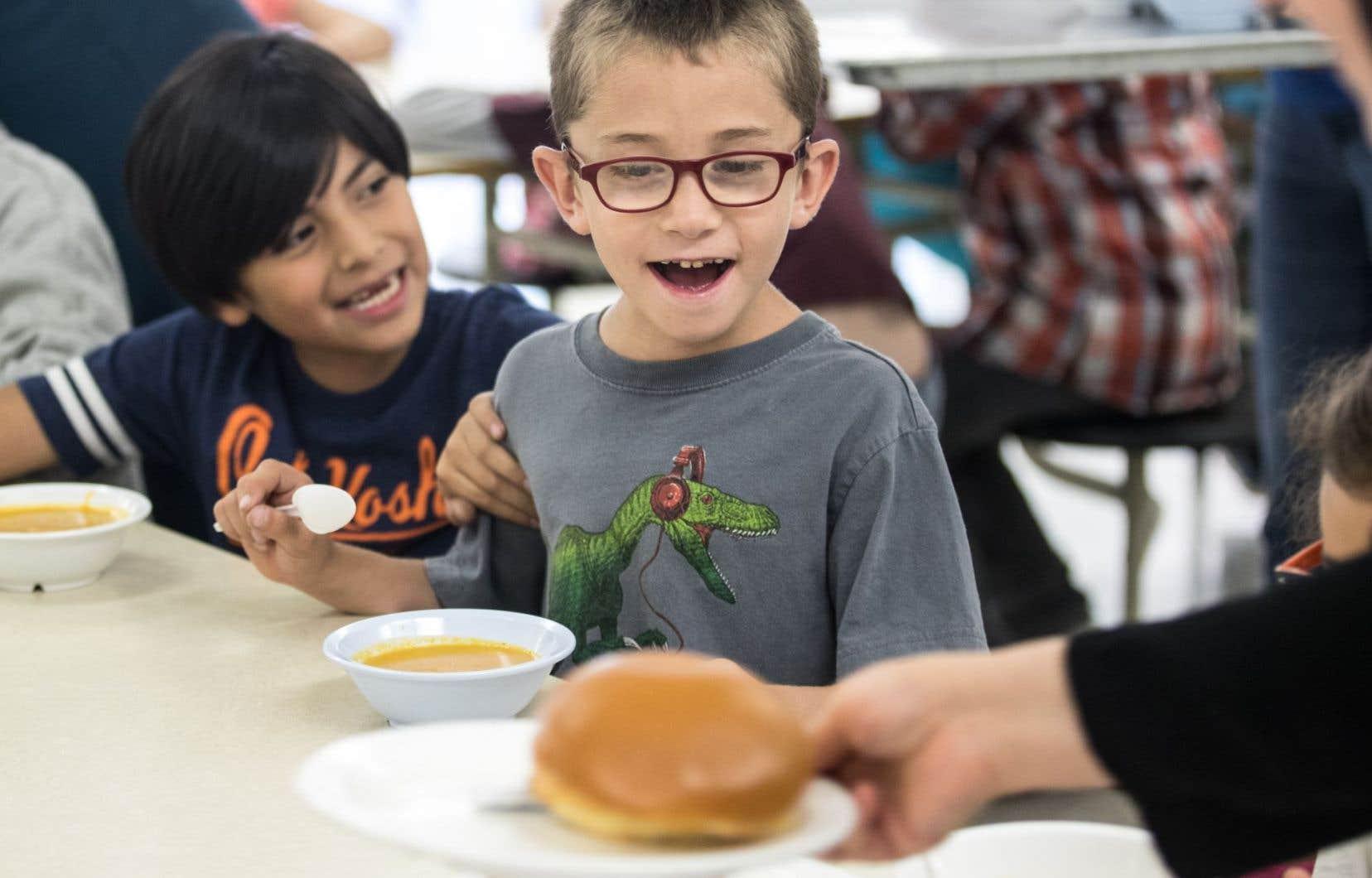 Ces enfants semblent apprécier le repas qui leur est servi à l'école Charles-Lemoyne, dans le quartier Pointe-Sainte-Charles à Montréal.