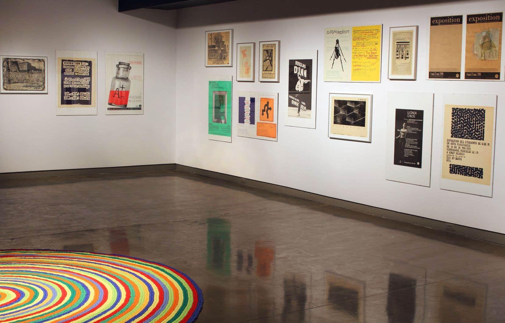 Vue de l'exposition avec des affiches annonçant des expositionsd'étudiants,1976-2000,avec, au premier plan, une vue partielle de «Copie» (d'après Claude Tousignant), 1992, de Marie-Josée Lafortune.