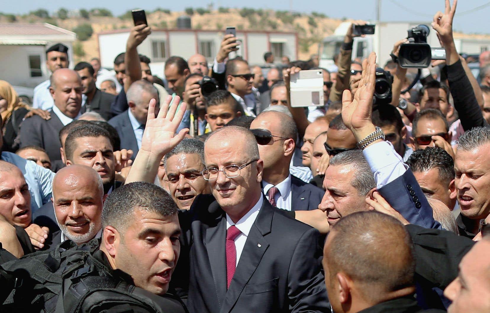 Rami Hamdallah (au centre) salue ses supporteurs, à son arrivée au poste-frontière d'Erez.