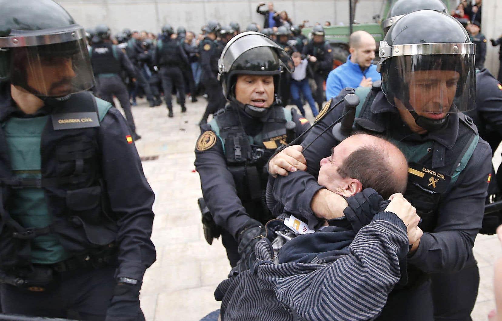 La Garde civile espagnole tire un homme à l'extérieur d'un bureau de vote à Barcelone.
