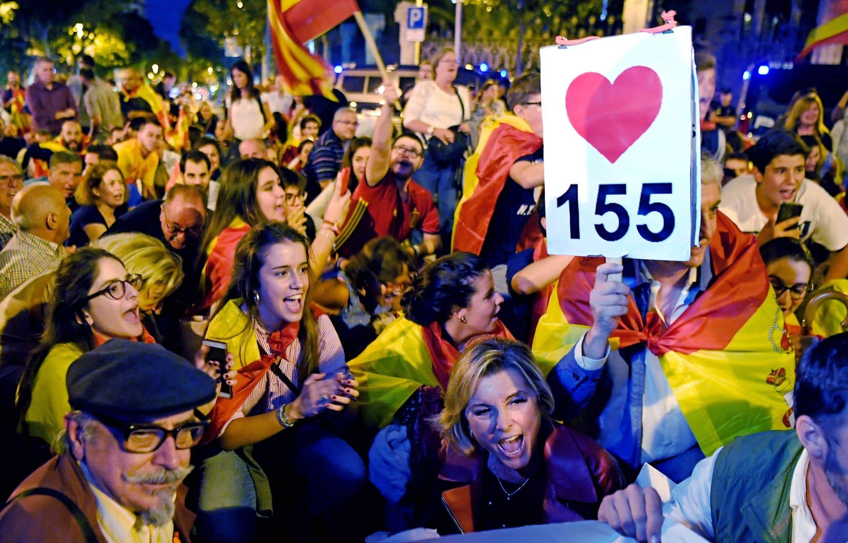 Des partisans de l'unité espagnole dans une manifestation à Barcelone — le «155» de la pancarte fait référence à un article de la Constitution qui donne au gouvernement central le droit de prendre la direction d'une communauté autonome.