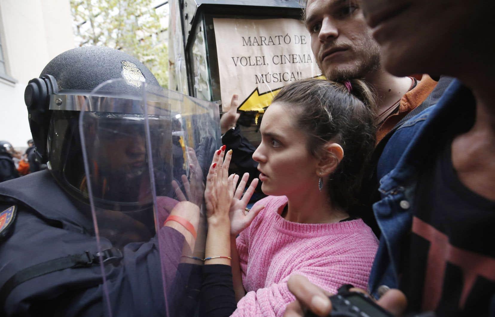 La Garde civile repousse des manifestants catalans en marge du scrutin référendaire, lors duquel le Oui l'a emporté à 90,18%.