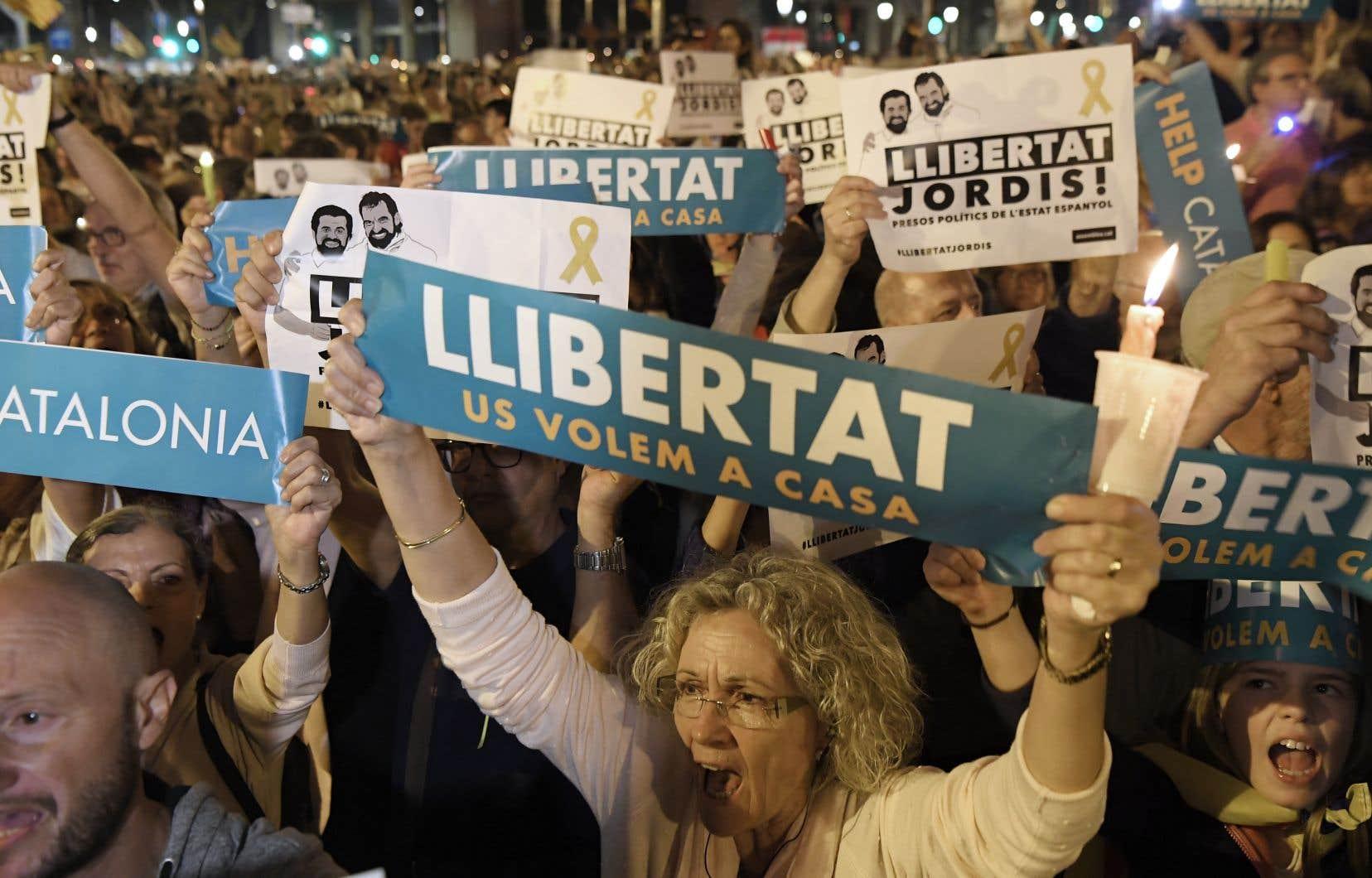 Des manifestations brandissent des pancartes en faveur de la «liberté» lors d'un rassemblement éclairé à la chandelle, mardi soir, à Barcelone.
