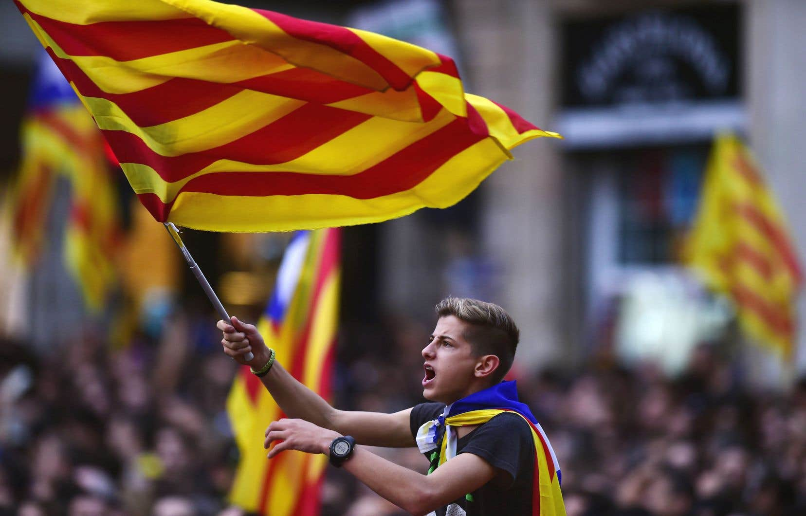 Un garçon agitant un drapeau catalan parmi la foule réunie place San Jaume. «Aujourd'hui, c'est le début de l'indépendance», chantaient les manifestants.