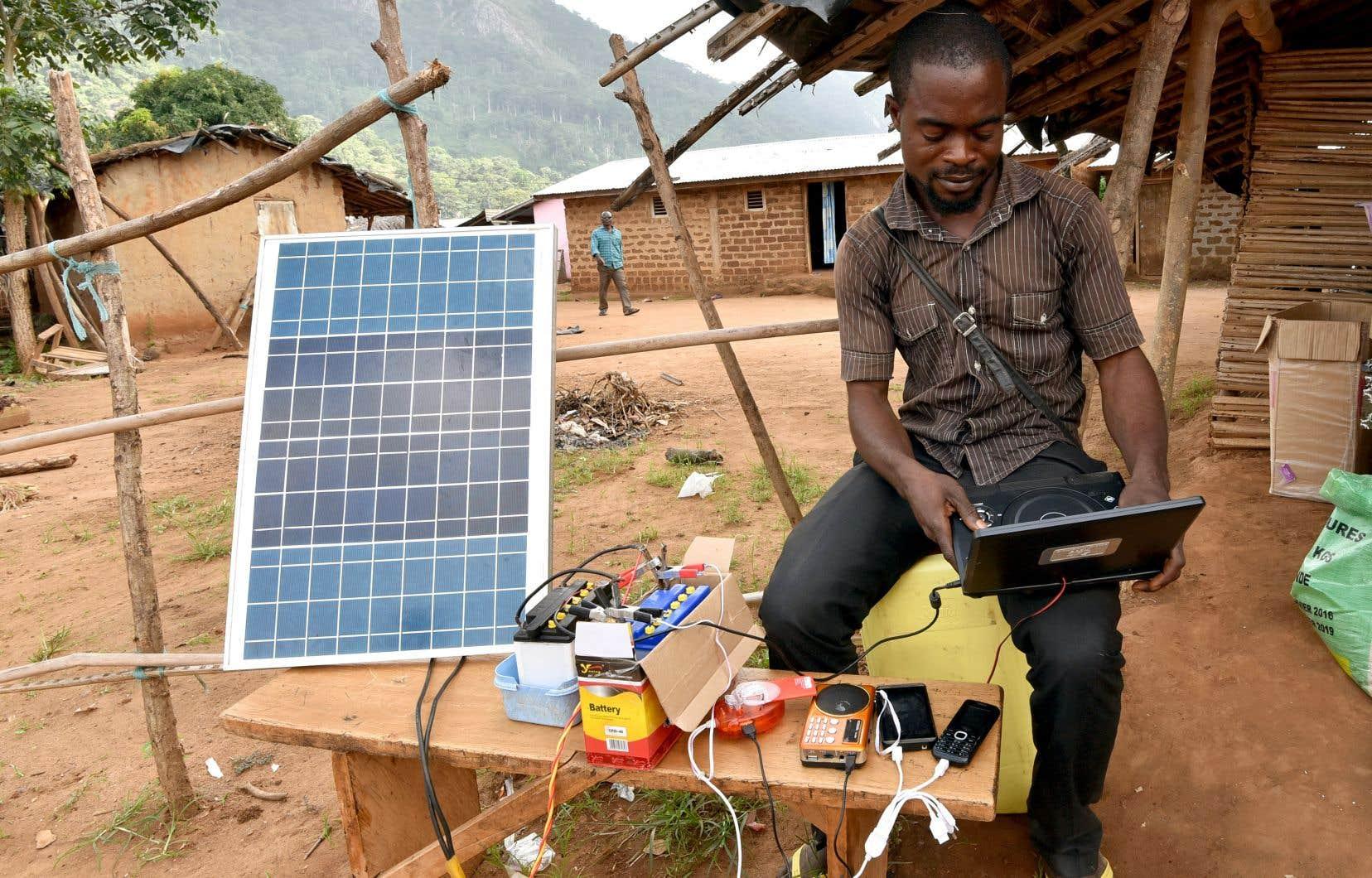 Un homme charge des appareils électriques à l'aide d'un panneau solaire à Diebly, un village sans électricité en Côte d'Ivoire. L'AIE estime qu'environ 675millions de personnes (à 90% en Afrique sub-saharienne) resteront sans accès à l'électricité en 2030, contre 1,1milliard aujourd'hui.