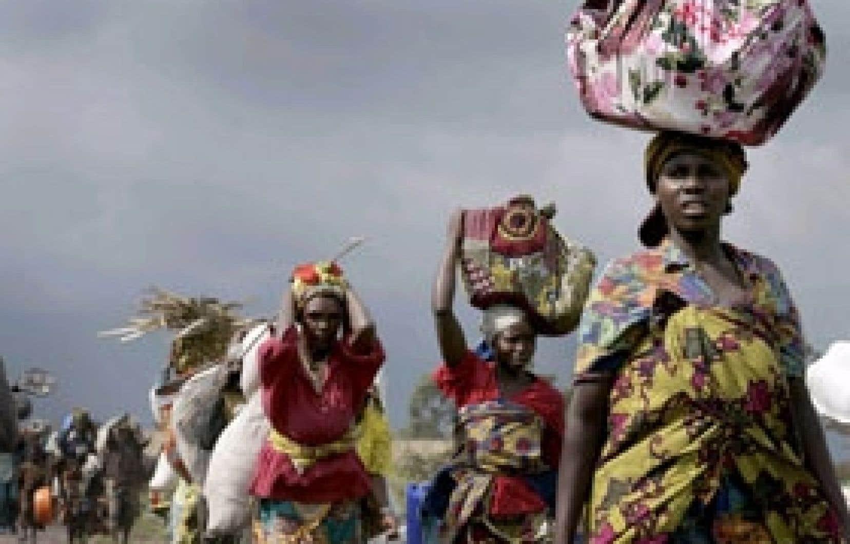 Une réfugiée congolaise s'agenouille en entendant des coups de feu, près de Kirbati, au nord de Goma.