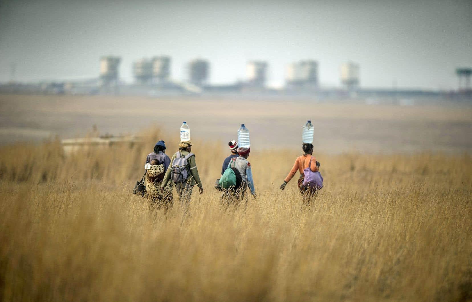 À Segunda, en Afrique du Sud, des femmes transportent de l'eau. Les femmes sont aux premières loges des impacts de plus en plus concrets des sécheresses, des phénomènes climatiques extrêmes, de la désertification ou alors de la raréfaction des ressources.