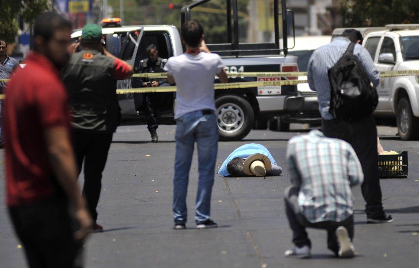Des passants prennent des photos du journaliste et écrivain mexicain Javier Valdez Cárdenas, tué par balles en pleine rue à Culiacán, dans l'État de Sinaloa, le 15mai dernier.