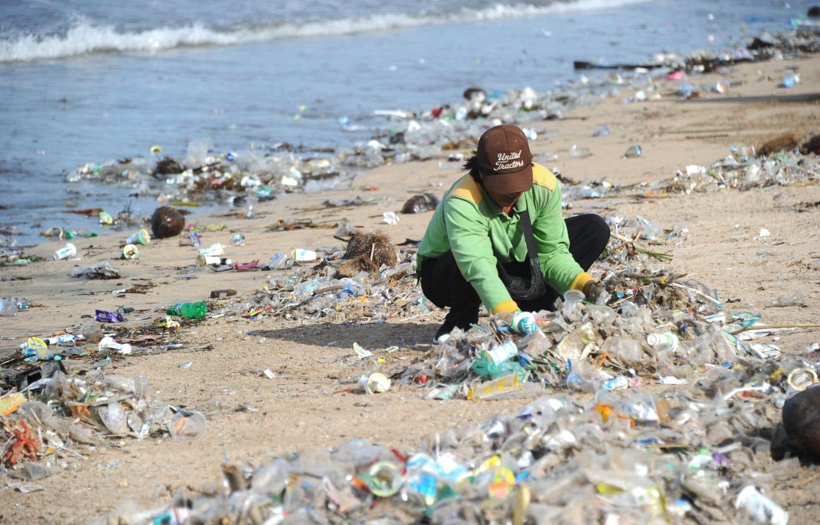 Cette photo prise le 19 décembre 2017 montre un ramasseur d'ordures qui nettoie la plage de Kuta près de Denpasar, sur l'île touristique de Bali, en Indonésie.