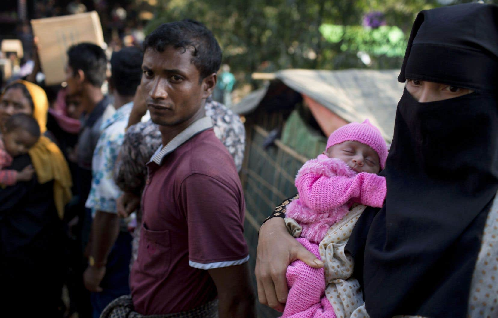 Une femme rohingya, qui a traversé le Myanmar, porte son nouveau-né et attend de recevoir de l'aide au camp de réfugiés de Kutupalong à Ukhiya, au Bangladesh, le 21 décembre.