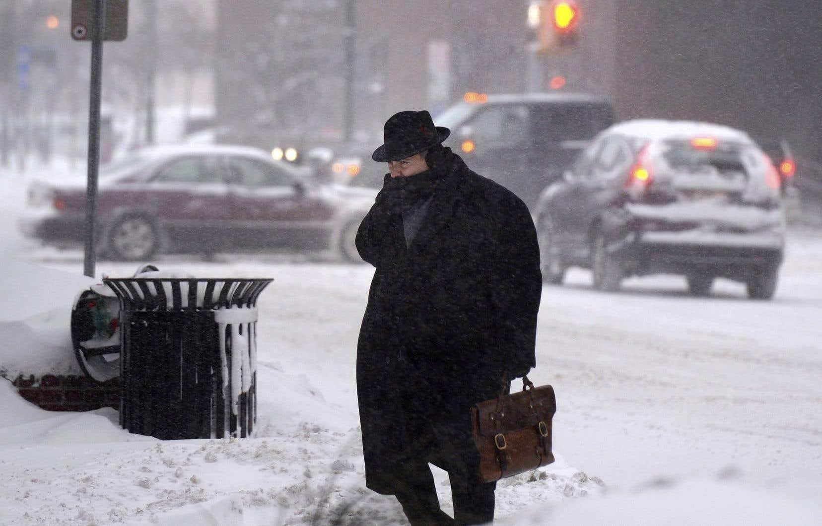 Un homme traverse la rue E. Washington au centre-ville de Syracuse, vendredi, endurant des températures ressenties avoisinant les -30°, parfois
