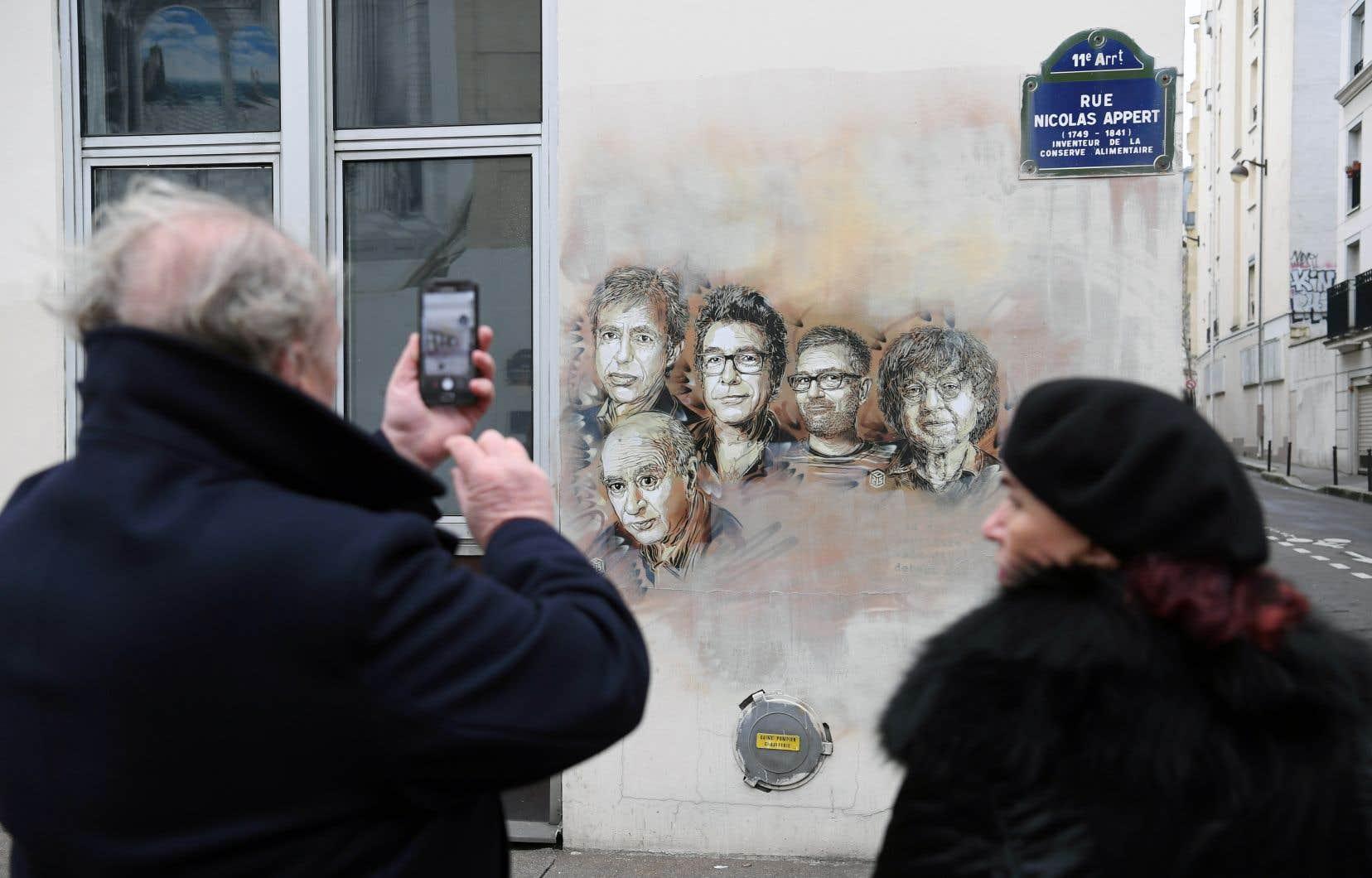 Des passants photographient les portraits des victimes et figures emblématiques de «Charlie Hebdo» près des bureaux de l'hebdomadaire sur la rue Nicolas-Appert, à Paris.