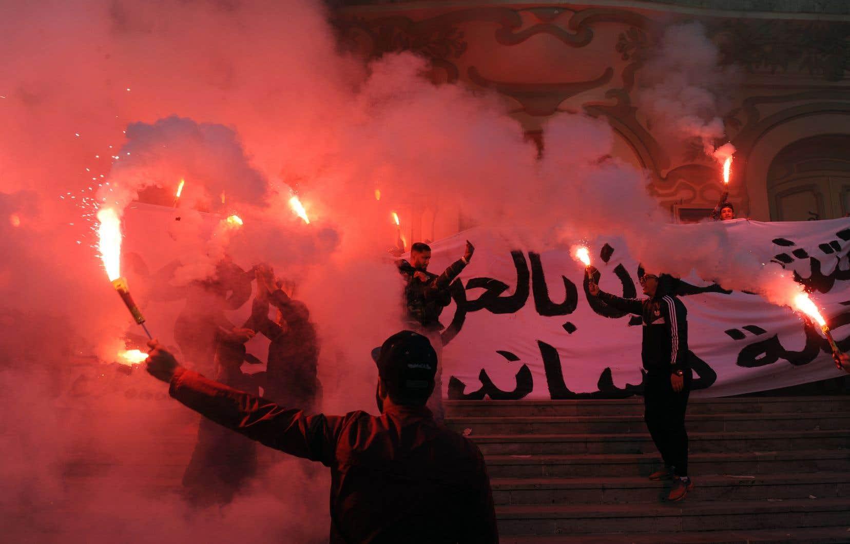 Des manifestants armés de fusées éclairantes ont protesté contre le gouvernement à Tunis, dimanche.
