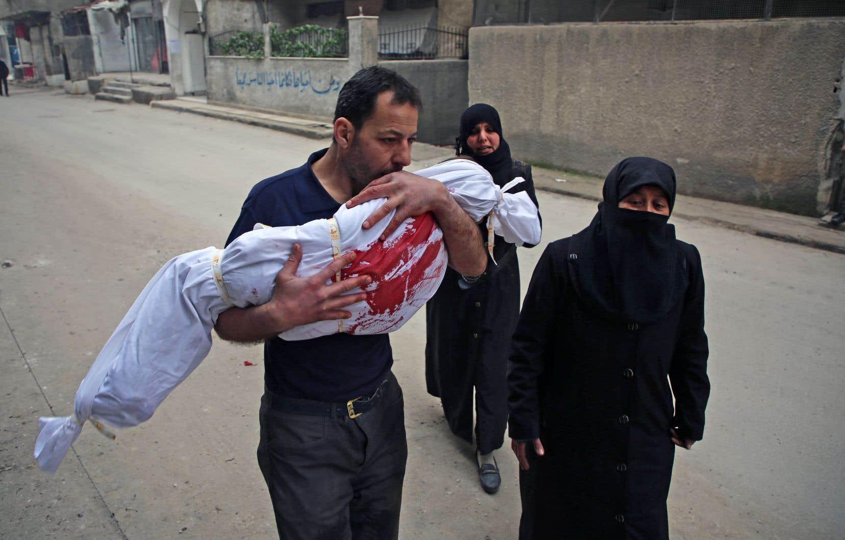 Un homme embrasse le corps de son enfant avant ses funérailles à Zamalka, près de Damas, lundi, à la suite d'un raid aérien.