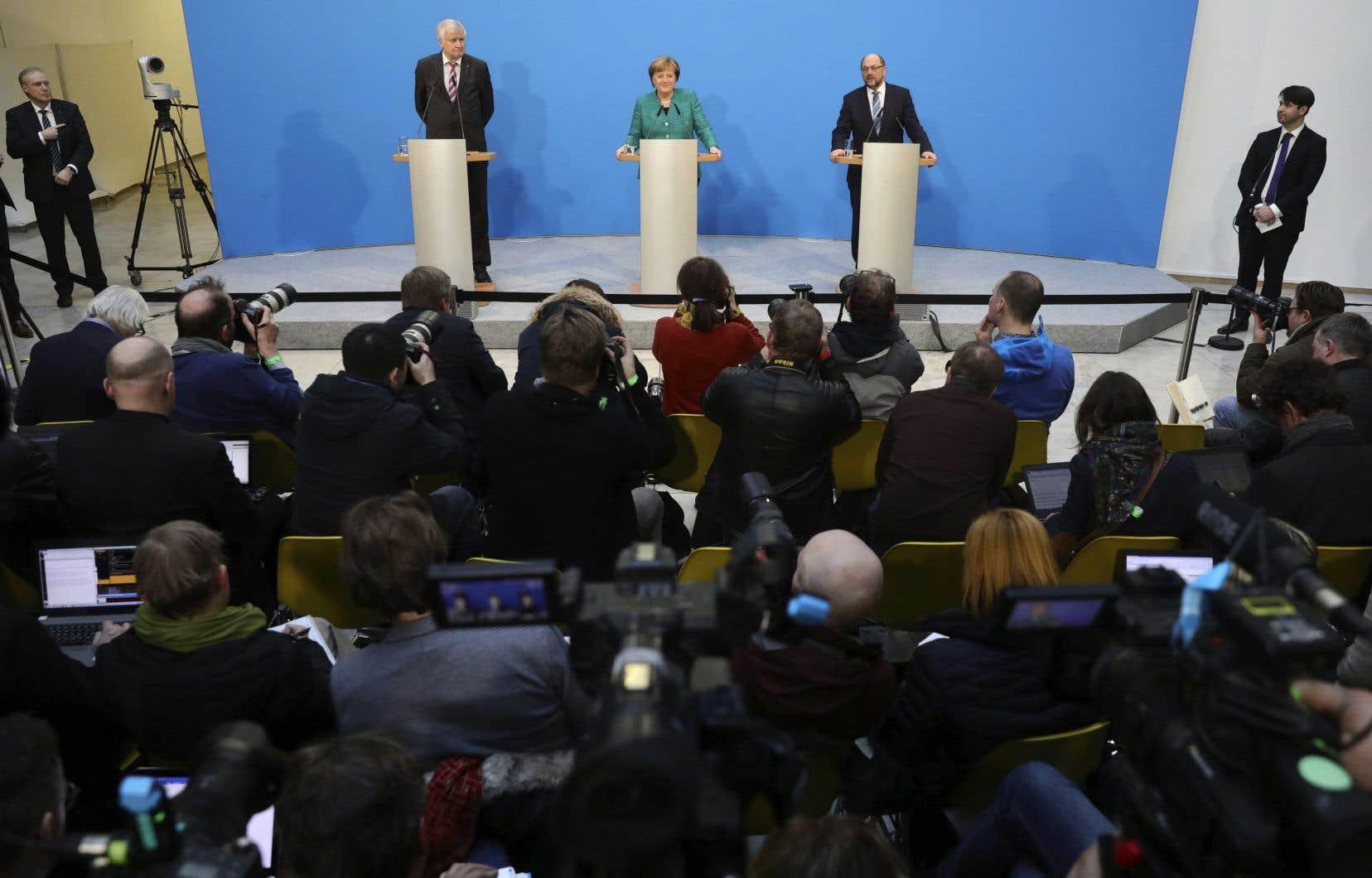 Angela Merkel, au centre, flanquée à droite du dirigeant social-démocrate, Martin Schulz, et à gauche de Horst Seehofer, de l'Union chrétienne-sociale en Bavière