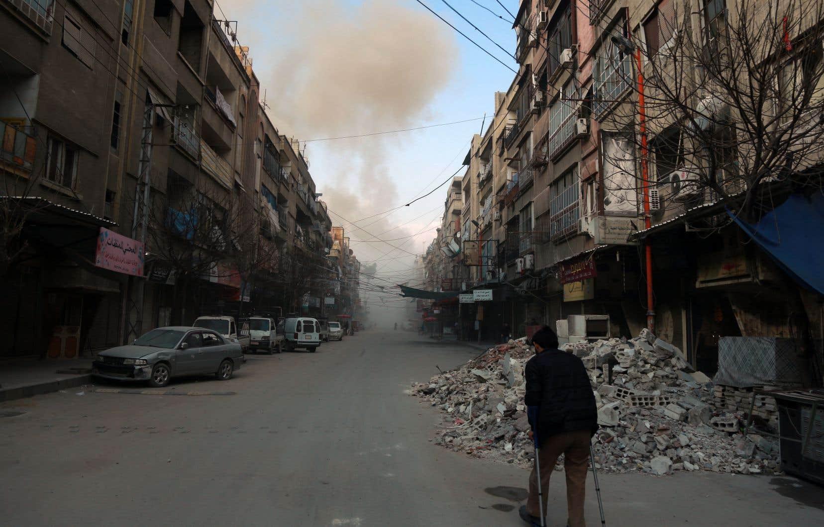Un homme syrien en béquilles dans une rue de Douma, une ville rebelle de la Ghouta orientale, peu après un raid aérien du régime syrien, vendredi
