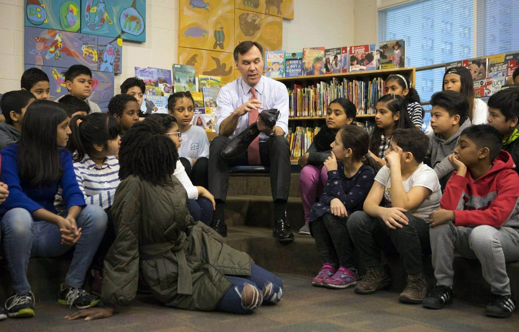 Bill Morneau a présenté ses nouvelles chaussures, conçues en Alberta et fabriquées au Mexique, à une classe du primaire de Toronto, jeudi.