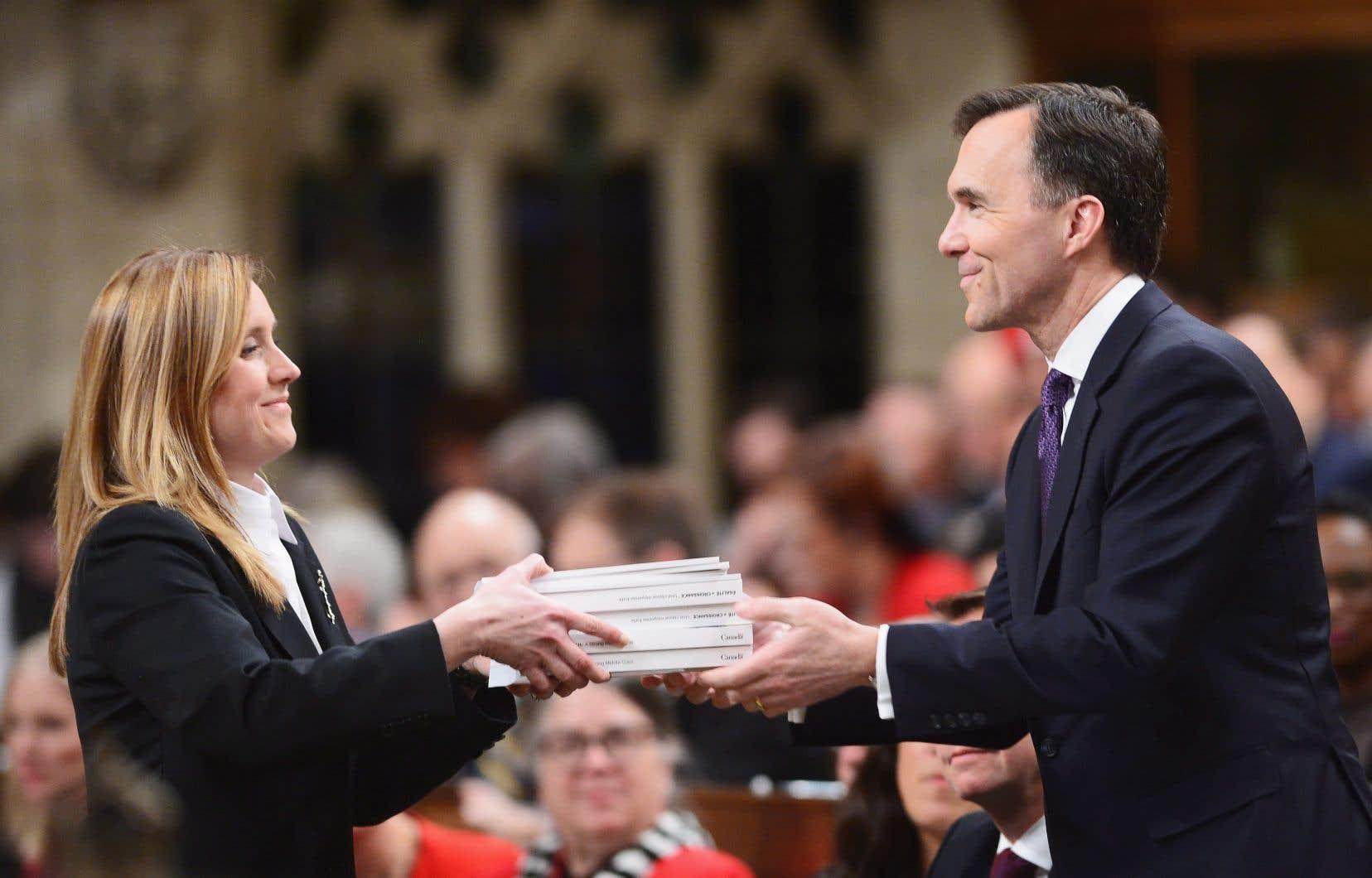 Le ministre des Finances, Bill Morneau, remet à une greffière de la Chambre des communes son troisième budget, que certains ont qualifié de féministe.