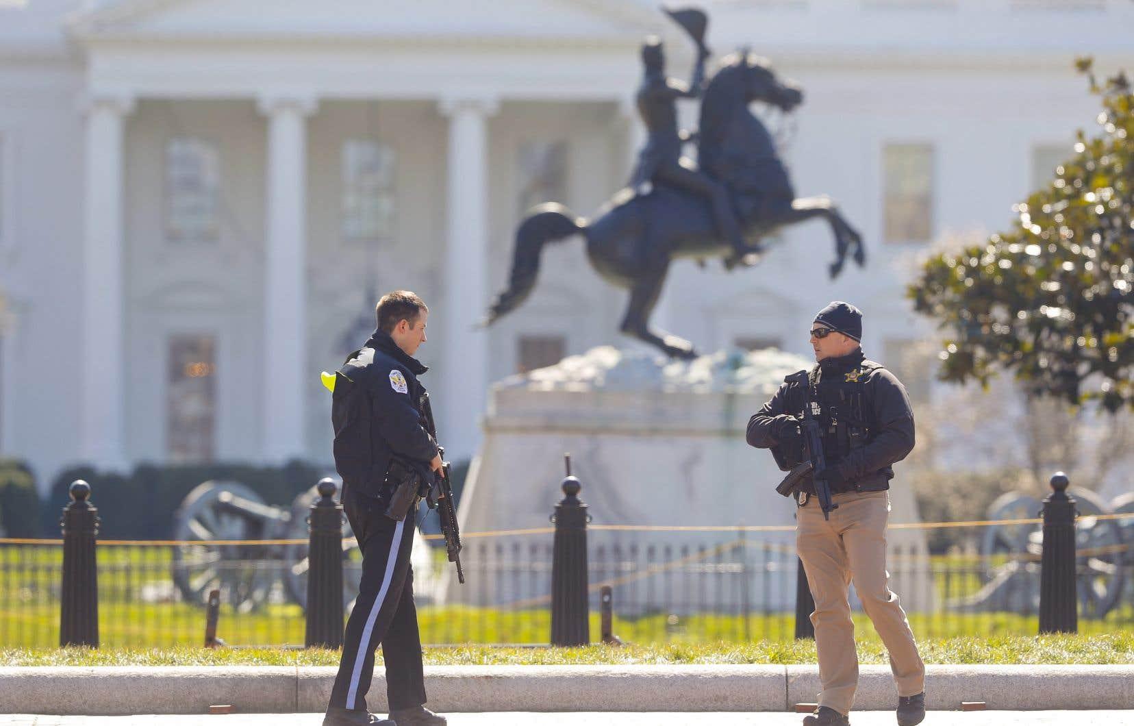 Des policiers montent la garde en face de la Maison-Blanche à Washington, samedi, après qu'un homme se soit enlevé la vie à proximité de la barrière nord.
