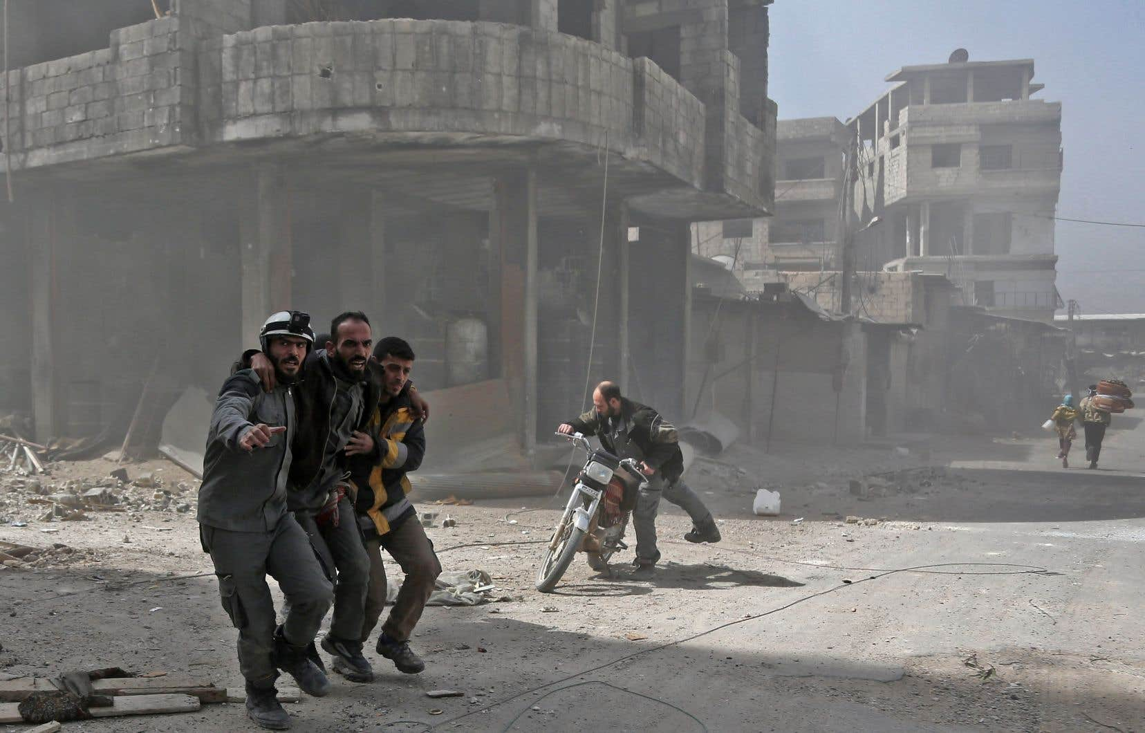 Des volontaires de la défense civile syrienne aident un homme à Hamouria pendant le bombardement du gouvernement de Bachar al-Assad sur des zones de la Ghouta orientale, mardi.