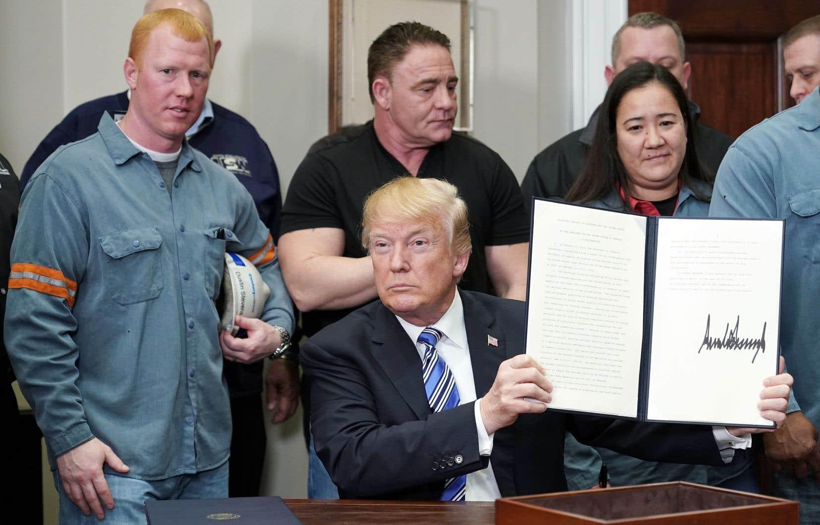 Le président américain, Donald Trump, montre la proclamation instaurant des tarifs sur les importations d'aluminium signée.