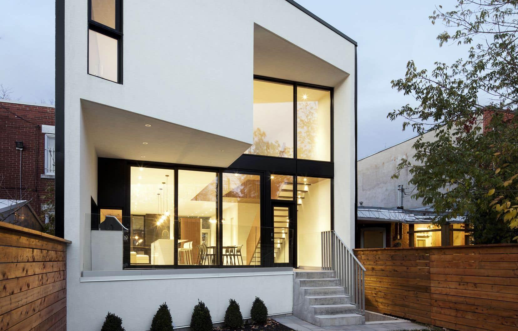 La fenestration de la façade arrière de la Maison 1ère Avenue, par Microclimat, permet de profiter de la luminosité et de créer une continuité vers l'extérieur.