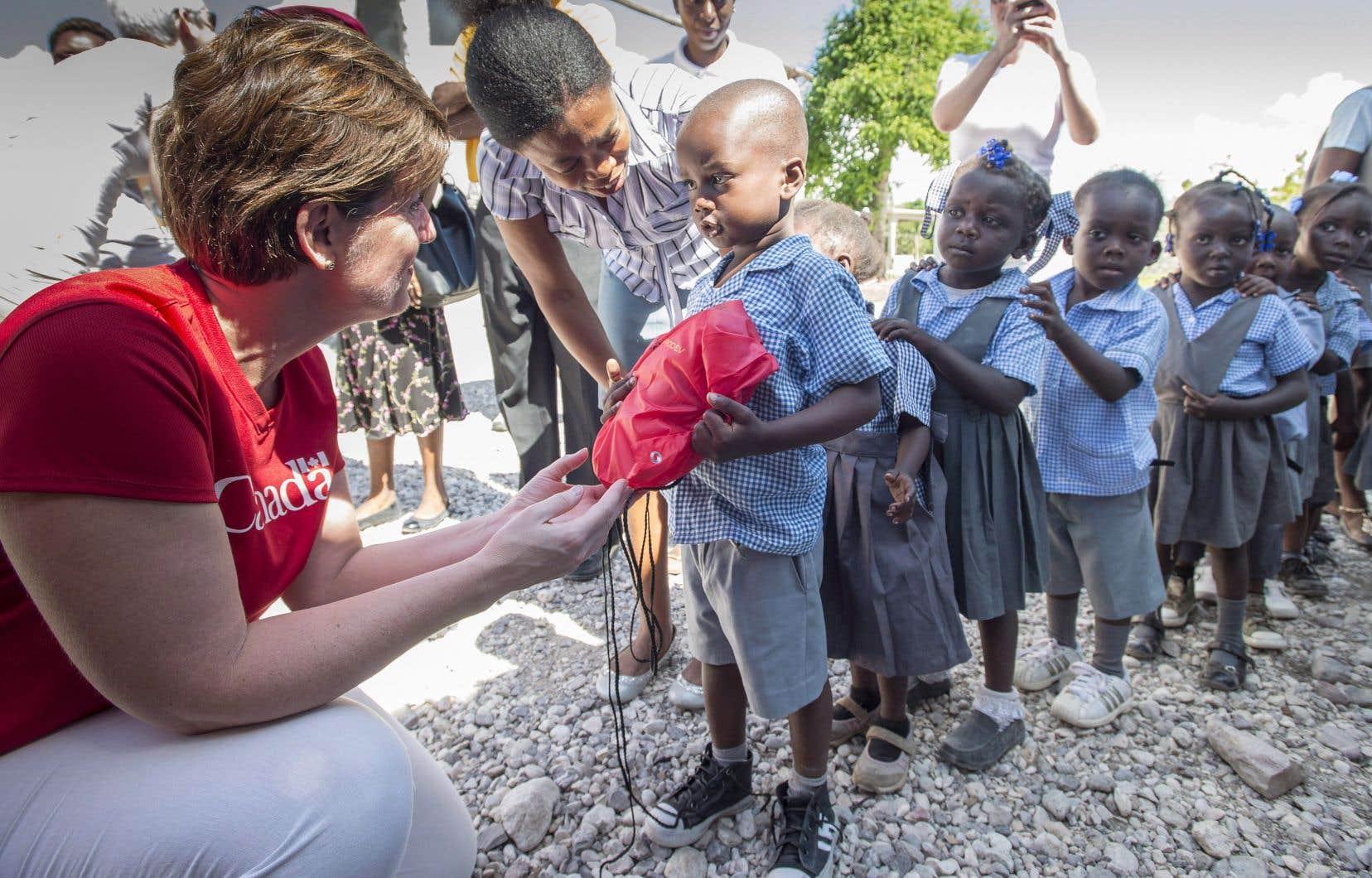La ministre canadienne du Développement international, Marie-Claude Bibeau, que l'on voit ici distribuant du matériel scolaire à des enfants haïtiens après le passage de l'ouragan «Matthew», en novembre dernier, réitère sa confiance dans les organisations humanitaires canadiennes.