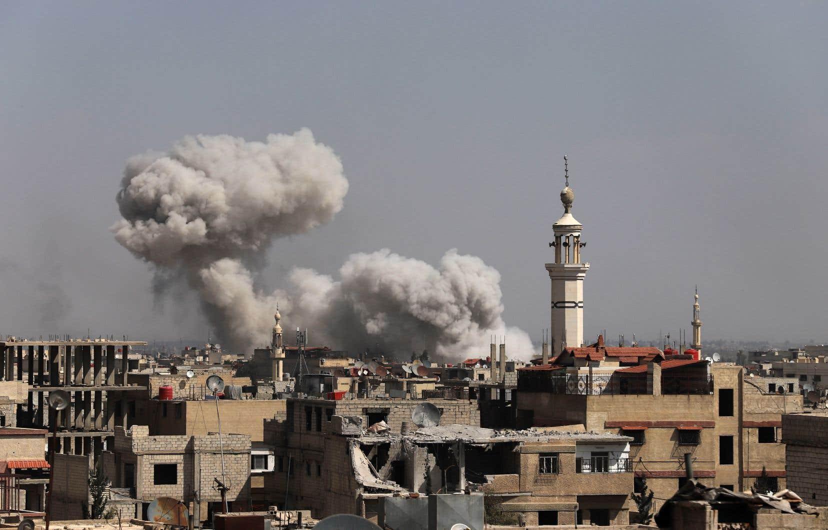 De la fumée s'échappe de plusieurs édifices dans la ville rebelle de Kafr Batna, en Ghouta orientale, à la suite des bombardements du gouvernement syrien dimanche.
