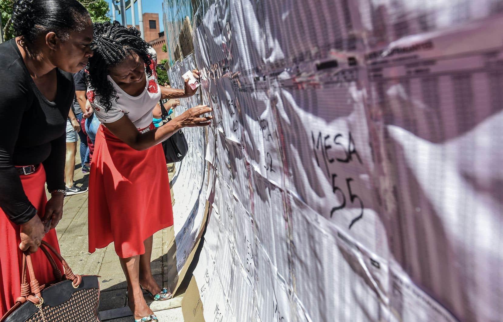 Deux femmes consultaient une liste électorale à Medellín lors des législatives de dimanche.