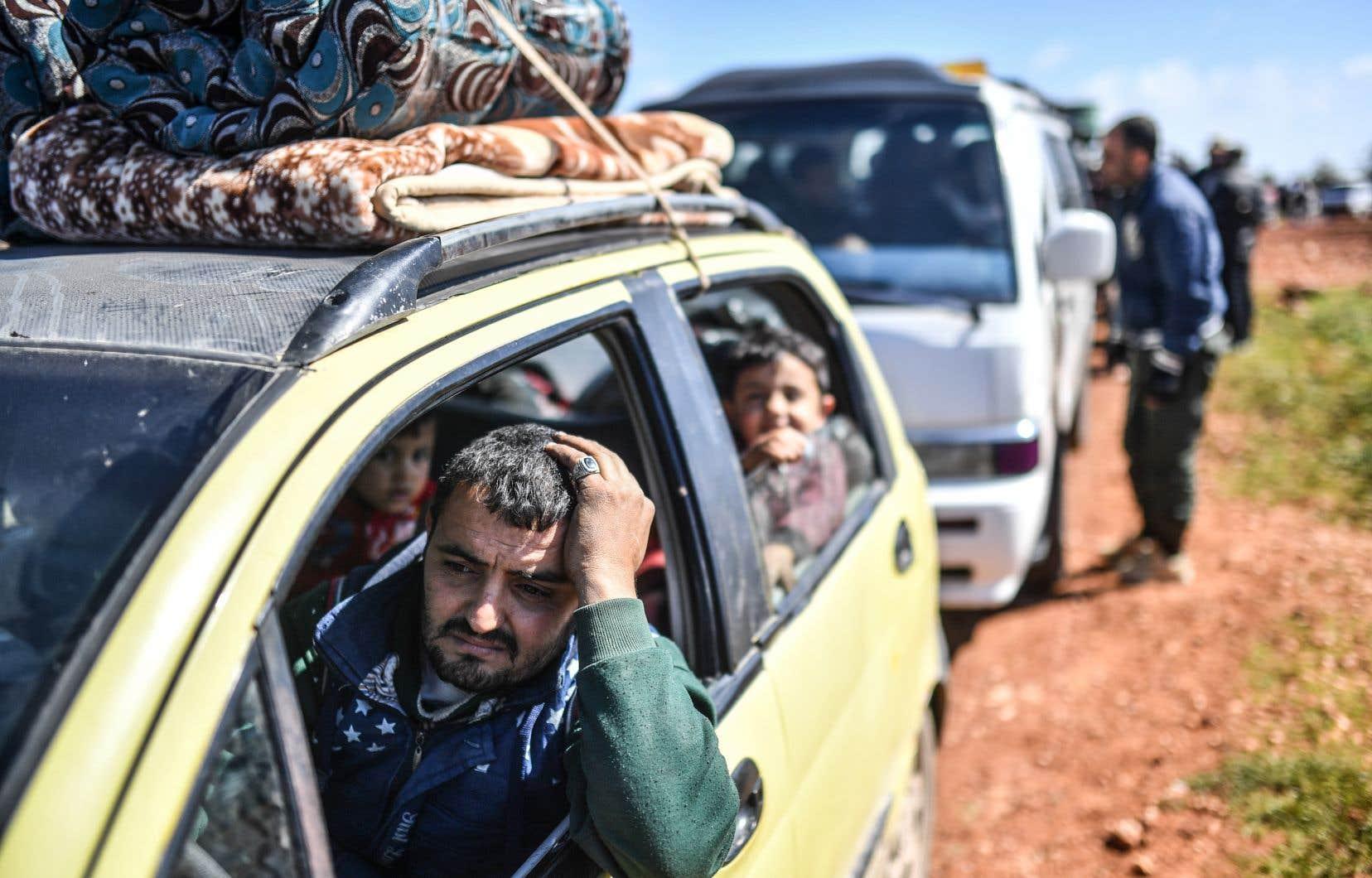 Des Syriens arrivent à un point de contrôle dans le village d'Anab, alors qu'ils fuient la ville d'Afrin dans le nord de la Syrie.