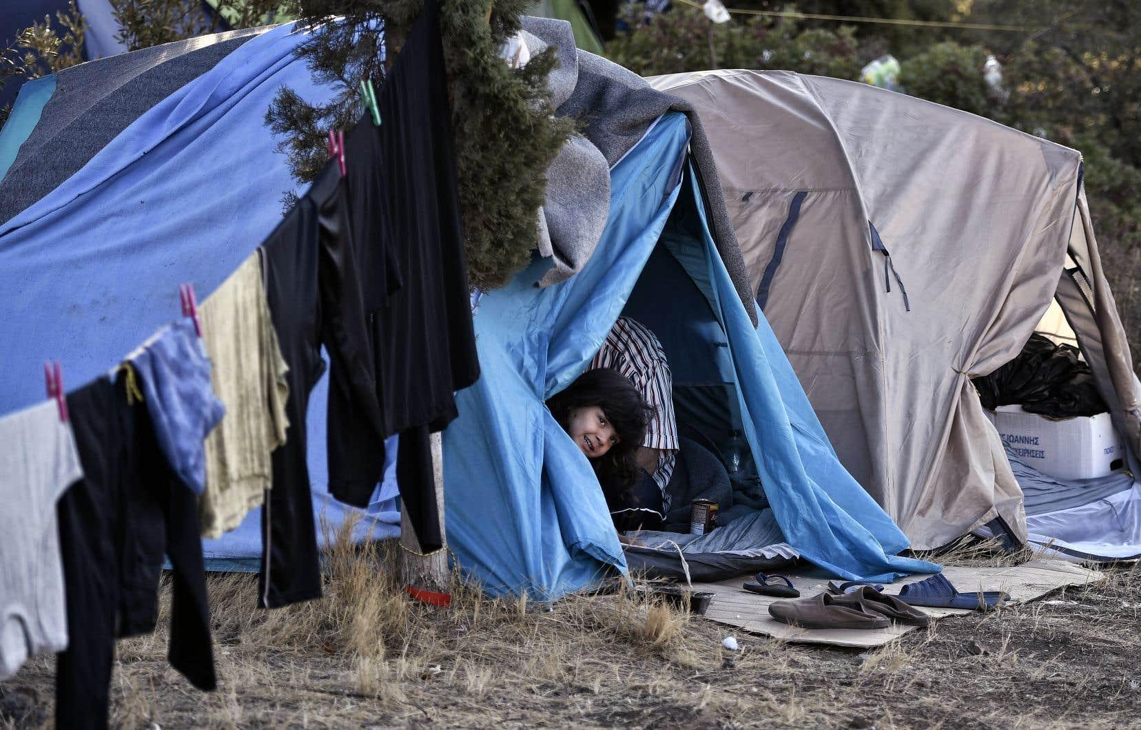 Une enfant regarde à l'extérieur d'une tente établie dans un camp de migrants sur l'île grecque de Samos.Les réfugiés piégés sur les îles grecques vivent dans des conditions sanitaires inacceptables, rappelle l'auteure.