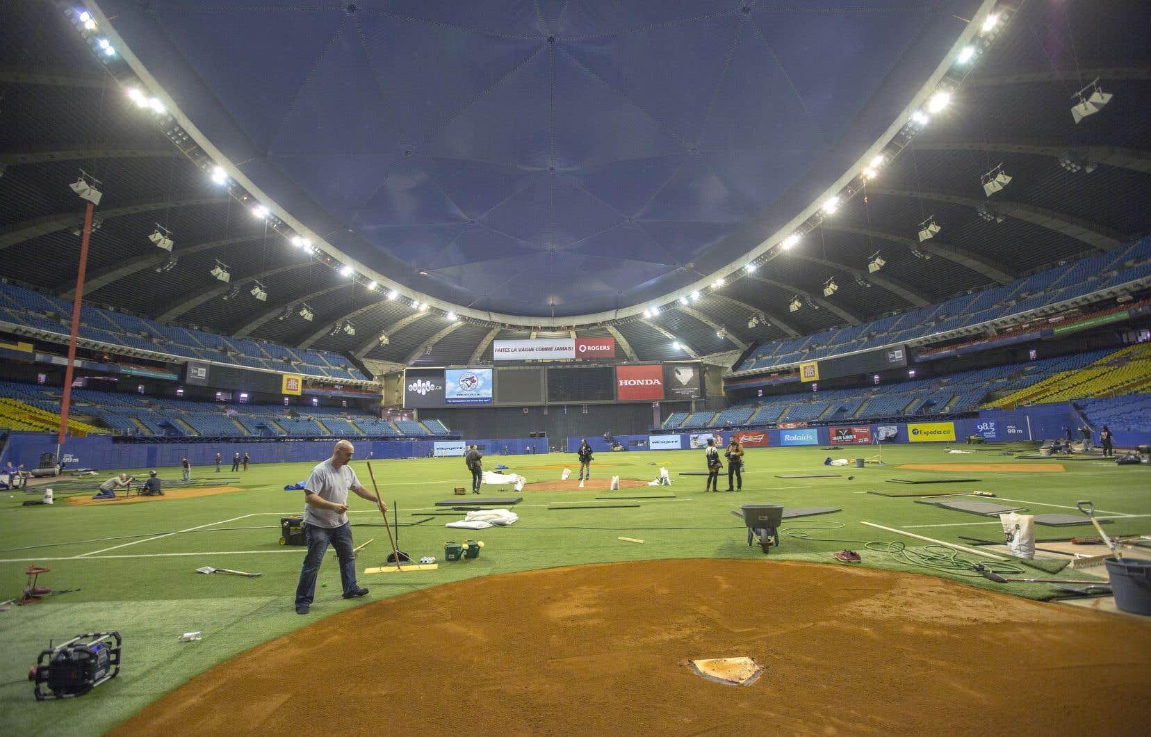 Des préposés préparent le terrain en vue d'un match de baseball, au Stade olympique de Montréal, en 2014.