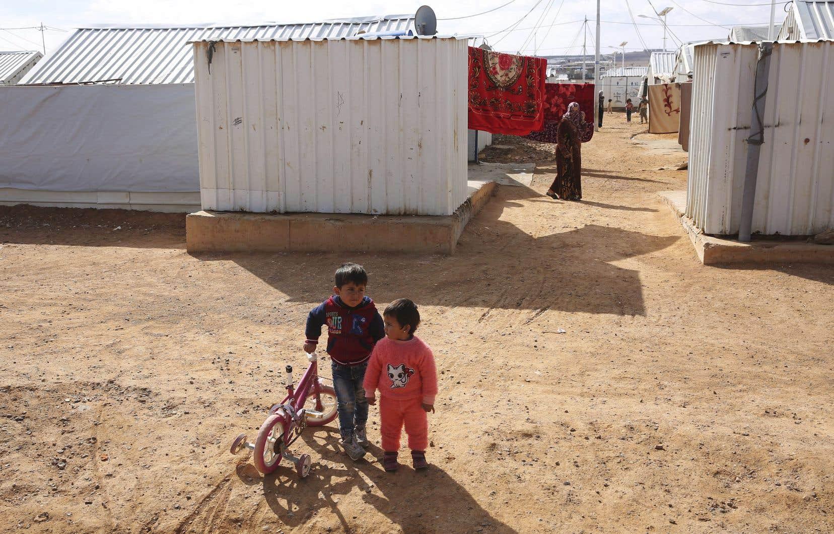 Deux enfants jouent dans un camp pour réfugiés syriens à Azraq, en Jordanie.