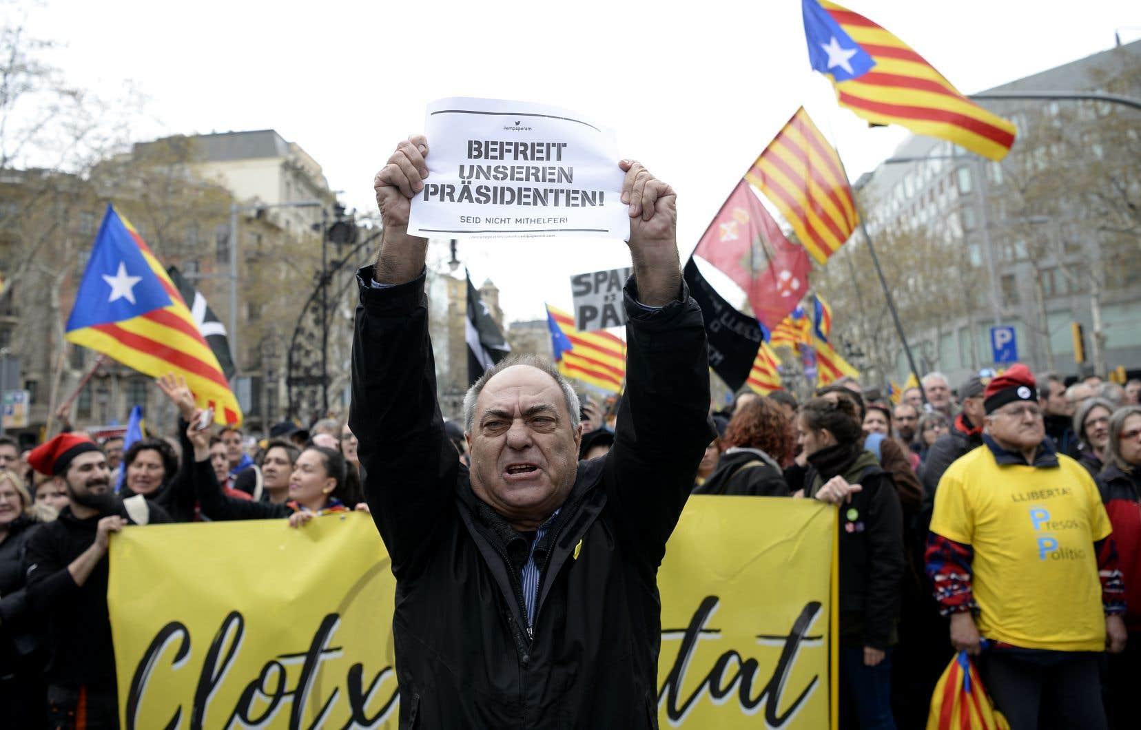 Un manifestant tient une pancarte en allemand disant «Libérez notre président» alors que d'autres brandissent des drapeaux de l'Estelada en faveur de l'indépendance catalane, dimanche, à Barcelone.