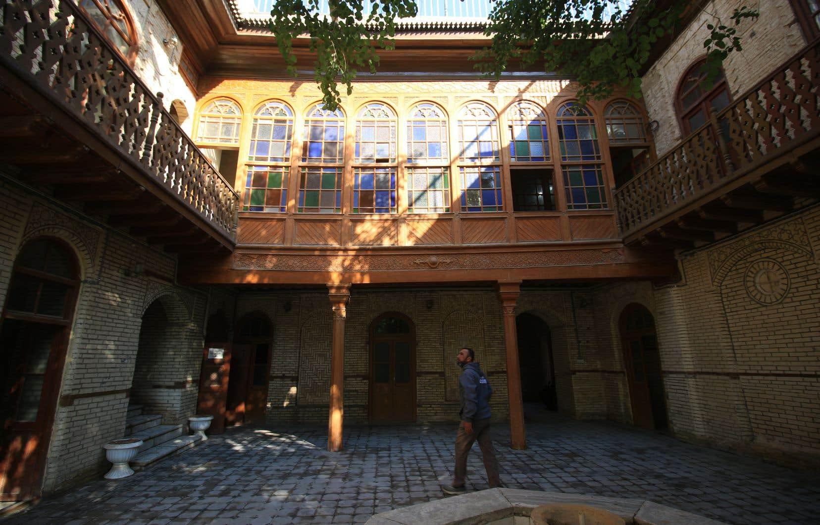 Un Irakien marche dans la cour intérieure d'une vieille maison patricienne aux fenêtres orientales ouvragées, appelées «chanachil».