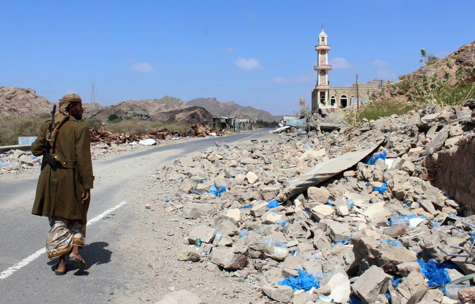 Un combattant yéménite loyal au gouvernement passe devant des débris, le long d'une route près de la ville d'Al-Shurayja.