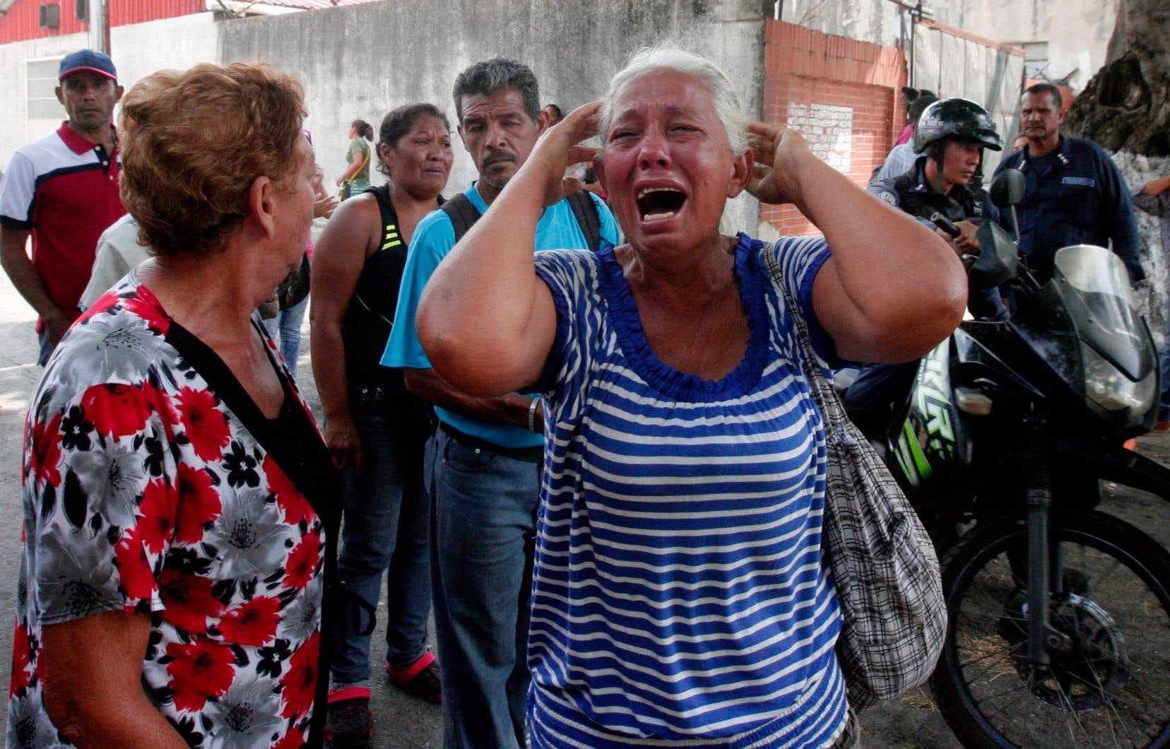 <p>Une femmeen pleurs devant le commissariat où l'incendie a eu lieu.</p>