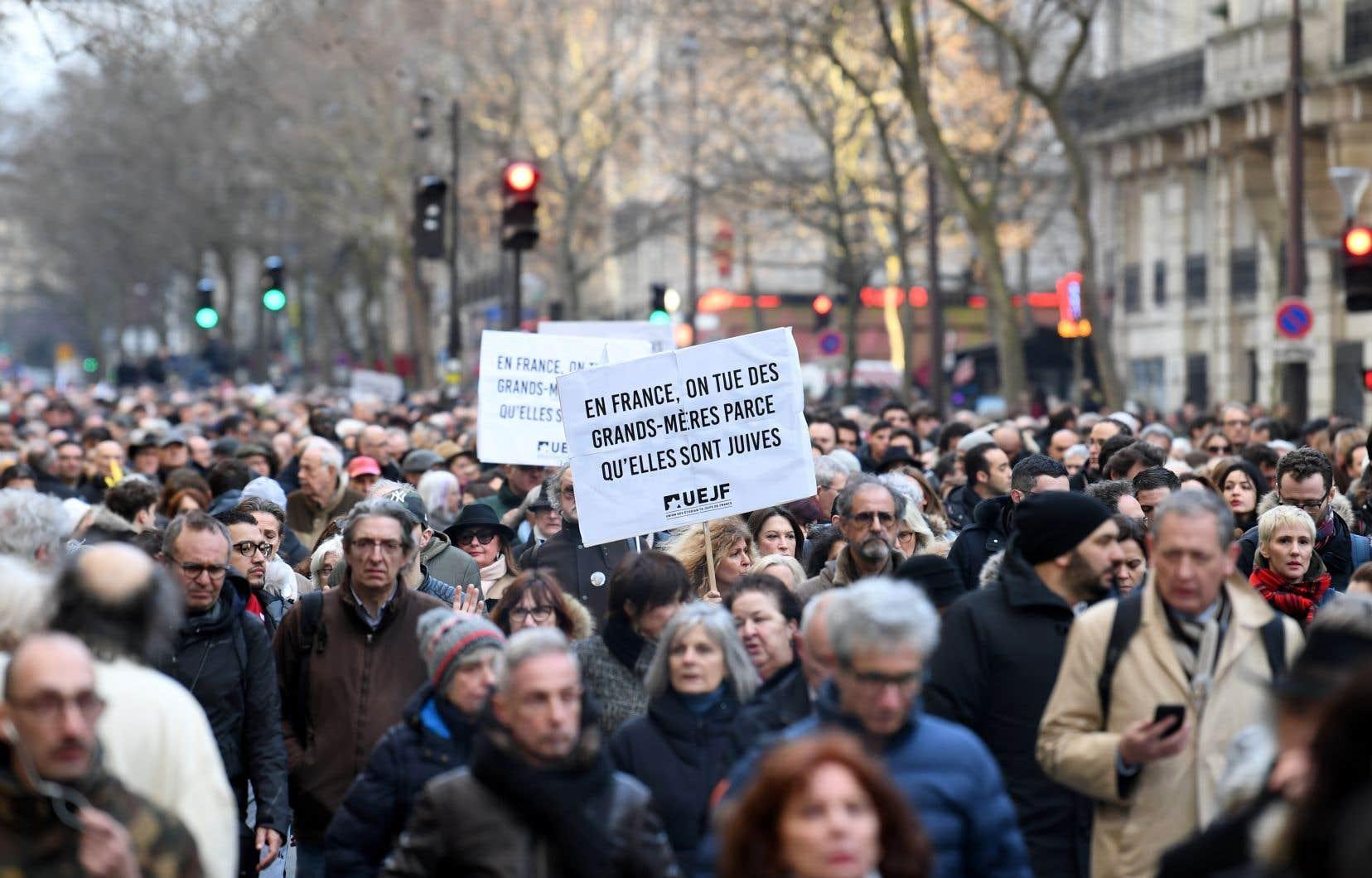 Des manifestants brandissent des pancartes lors d'une marche à Paris, mercredi, à la mémoire de Mireille Knoll, une femme juive de 85 ans assassinée chez elle dans ce que la police croit être une attaque antisémite.