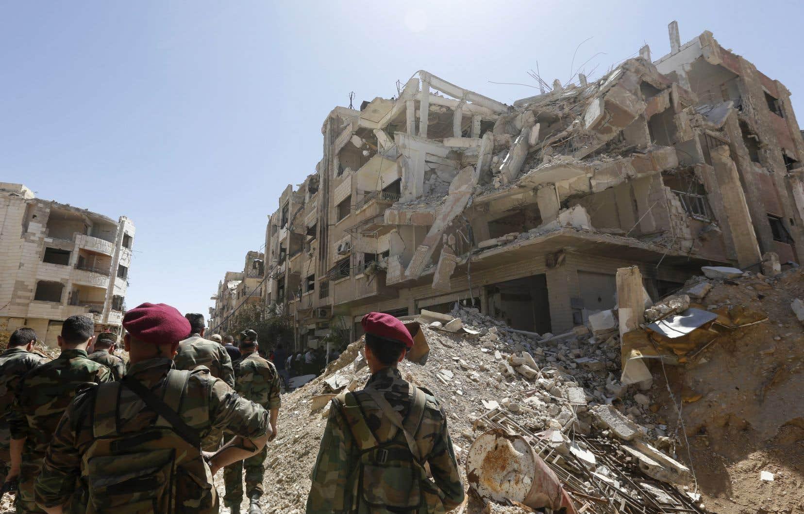 Des membres des forces syriennes marchent lundi au milieu des destructions dans le Jobar, zone de la Ghouta orientaleautrefois tenue par les rebelles.